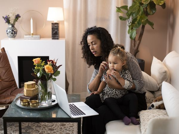 Worried mother looks at laptop screen on coffee table with toddler on her lap
