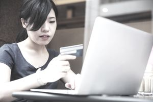 Woman with neutral expression using her credit card online