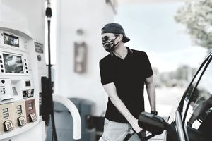 Adult man pumps gas wearing protective face mask during COVID-19 pandemic