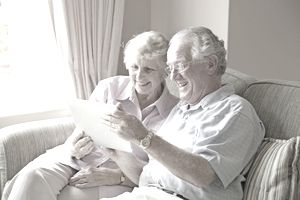 Couple using tablet computer in retirement home