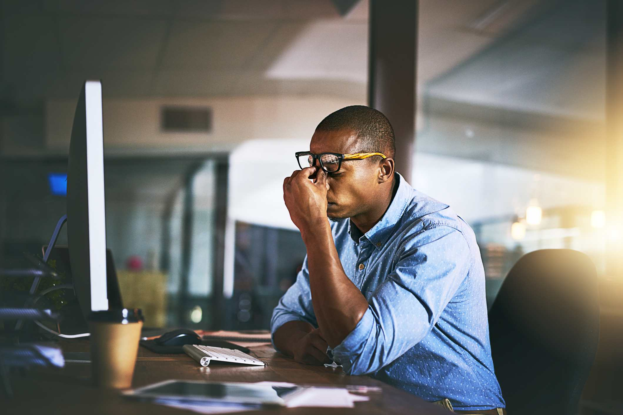 a young businessman pinching top of his nose and experiencing stress during late night office work