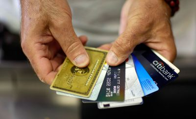 Man holding several credit cards with various interest rates