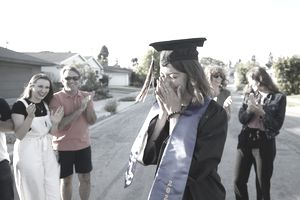 Graduating Woman in Black Cap and Gown and Blue Sash Covers Her Face While Friends Surround Her Outside