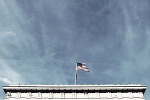 Low Angle View Of American Flag On North Carolina State Capitol Against Blue Sky