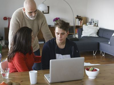 Parents talking with son by table with laptop at home.