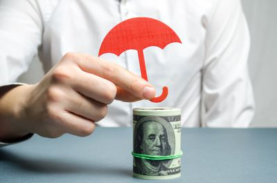 An umbrella is placed over a roll of bills to protect it from risky investments