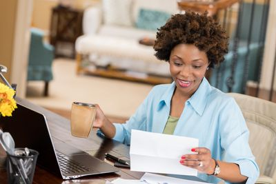 Smiling woman at home desk with coffee, looking at paperwork