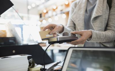 Why some stores dont take credit cards customer paying at credit card reader in market reheart Choice Image