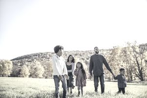 Young family of five walking through meadow in Autumn