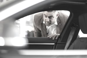 Person in brown suit sticking head through car window