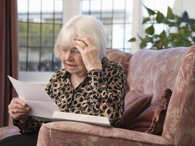 Older woman reads a notice at home while looking concerned.