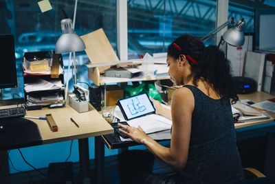 Female business owner calculating bills in industrial office