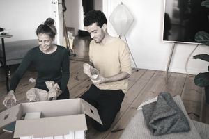 Couple removing glasses from box in living room at new home
