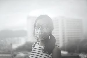 Young woman wearing protective face mask outdoors due to the polluted air