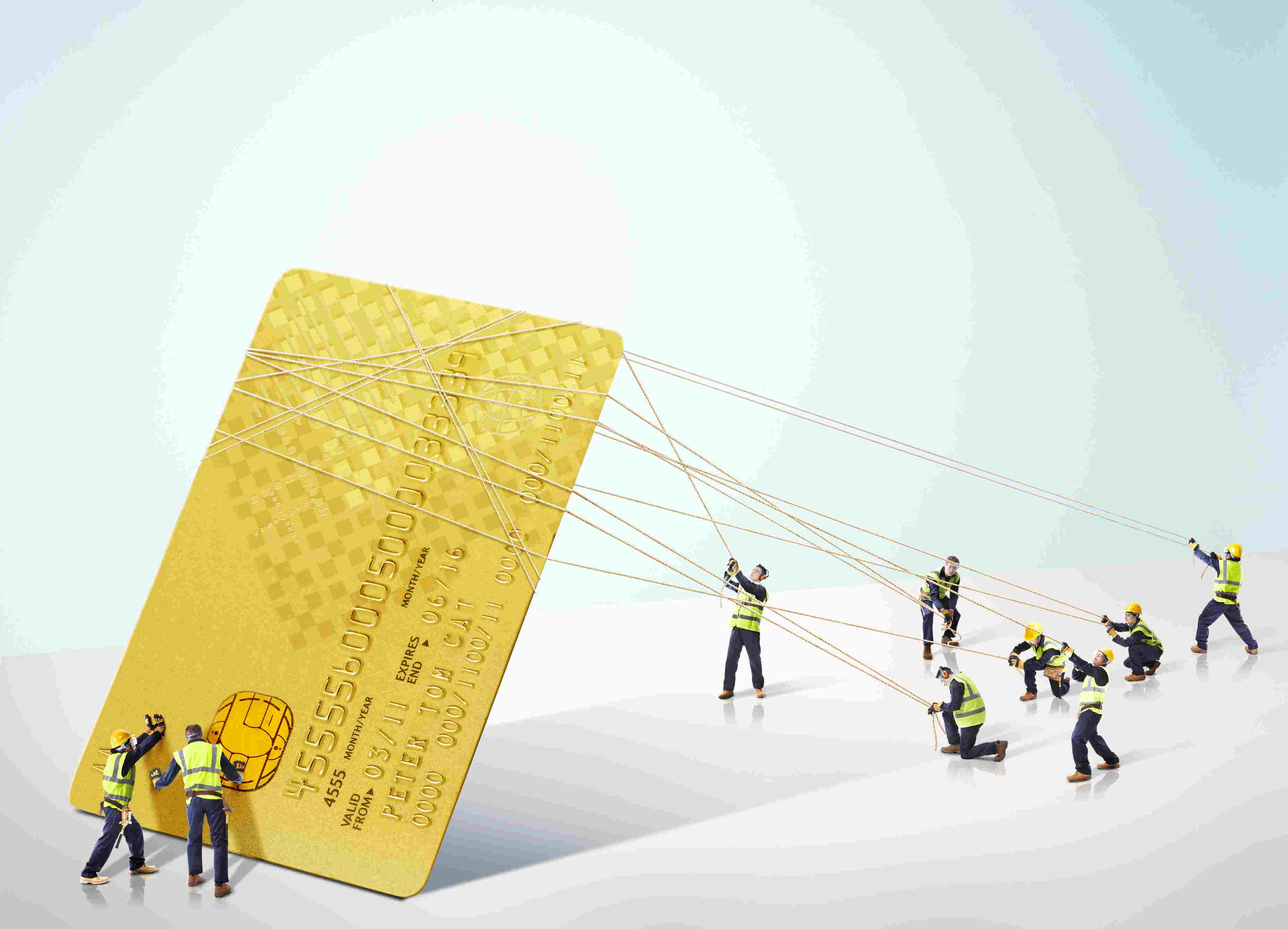 Group of builders carrying a giant credit card