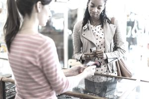 Woman paying for jewelry with contactless payment technology in a clothes store
