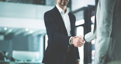Man in a suit shaking hands with another person in an office