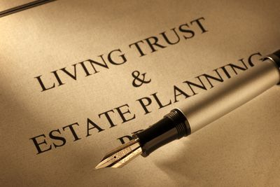 A fountain pen rests on a living trust & estate plan document