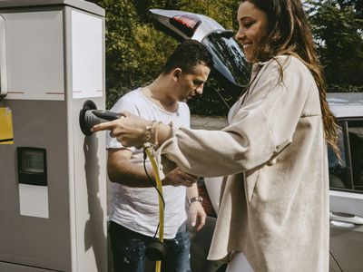 Smiling Woman Holds Electric Plug to Charge Her Car at Filling Station