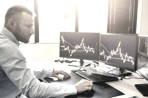 A day trader at his desk watching the market on his computer screens