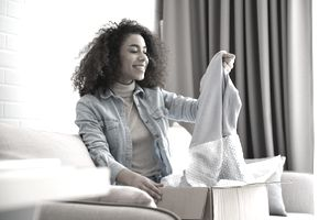 person in jean jacket sitting on couch opening a package