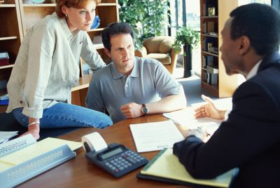 Consultant or advisor with calculator on table talking to a couple.