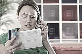 Woman on the phone holding credit card and billing statement