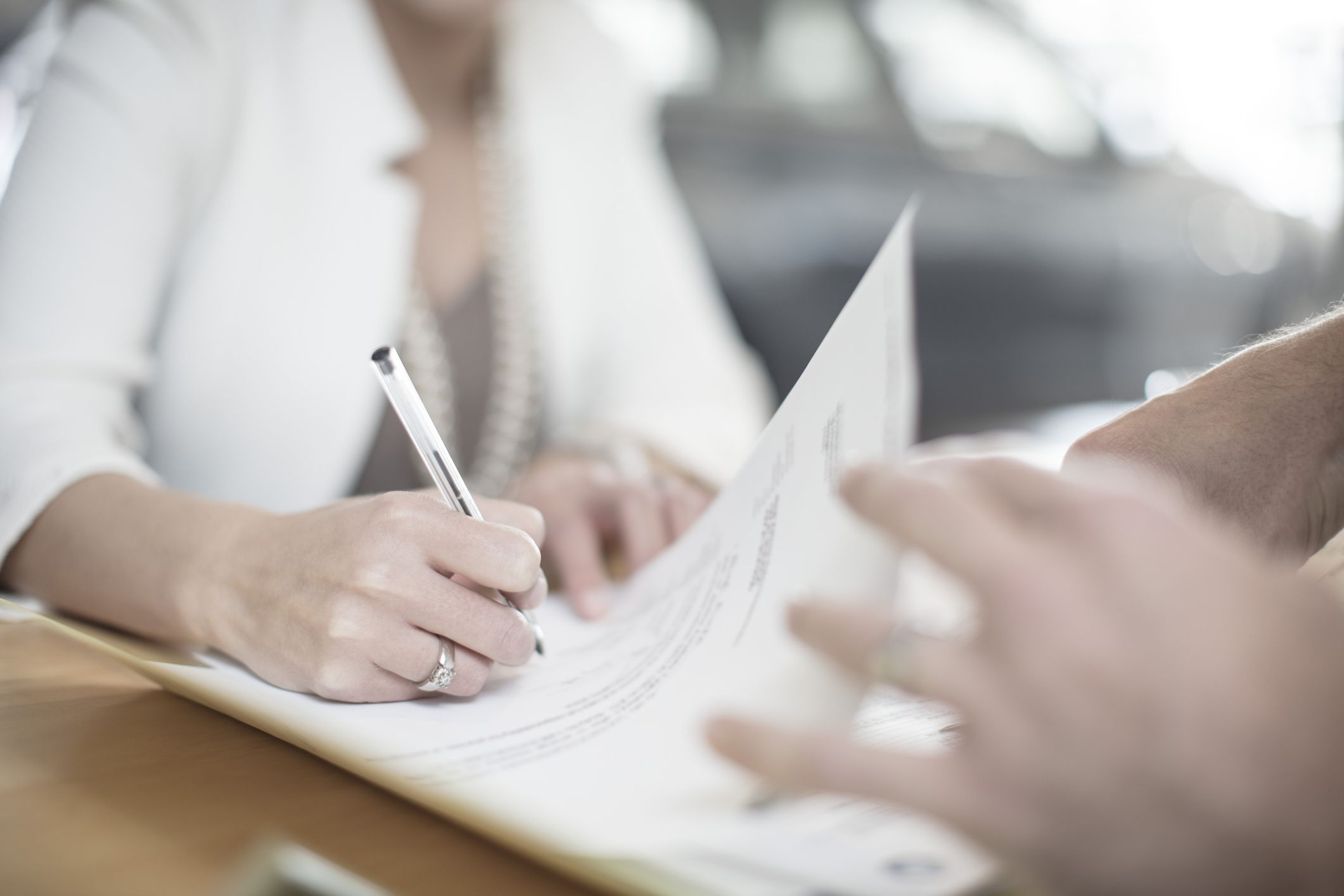 Woman signing forms and letter to insurance company