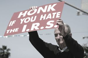 J. D. Montgomery holds a sign on the street outside of the James C. Corman Federal Building encouraging motorist to express their anger at the Internal Revenue Service (IRS) on their final day to file 2005 income taxes on April 17, 2006 in Van Nuys, California.