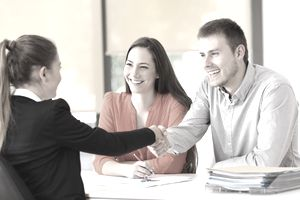 Couple closing on a new home loan, shaking hands over a table