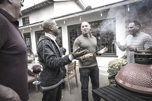Men standing by barbecue grill talking