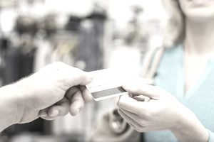 a woman handing a man her debit card