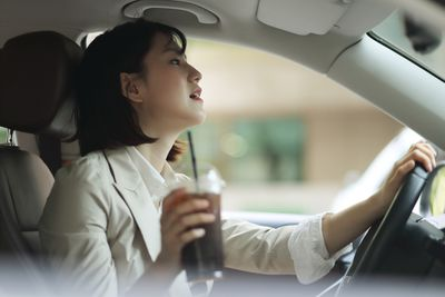 Businesswoman Driving With Ice Coffee