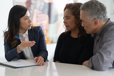 A couple discusses financial decisions with their investment advisor