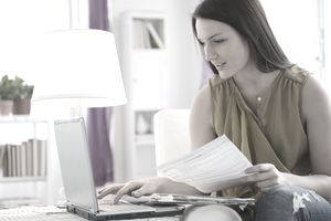 Young woman inputting information from a tax form on a laptop