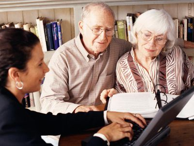 An older couple meeting with a female professional at a laptop