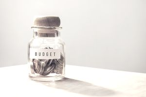 "Jar labeled ""Budget"" that is half-filled with coins, motivation to stick to your budget"