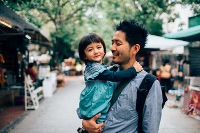 Coparent exploring a farmers market with his child