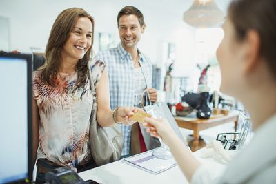 Couple smiling as they pay for their purchase using a portion of their tax return in a store