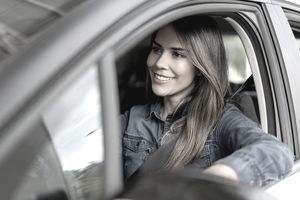 Smiling young woman behind the wheel of a car.