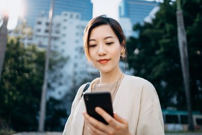 A woman looks at a cellphone with high rise buildings in background