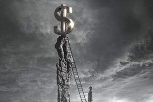 Man at foot of ladder leading up to a dollar sign on top of a mountain.