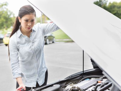 A woman is looking under the hood of her car.