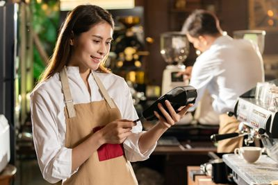A woman wearing an apron standing near an espresso machine inserts a chip card into a handheld chip-card reader.