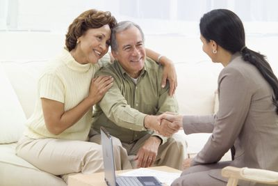 Smiling retired couple meeting with a professional in their home