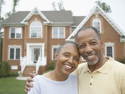 Two people stand in front of a house