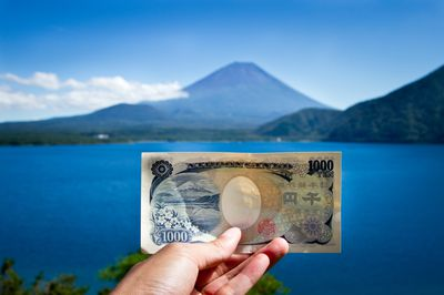 a hand holding up Japanese yen currency
