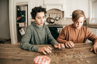 Two kids count coins laid out on a kitchen counter