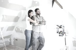 A man and a woman step back from their work drywalling a room and smile.