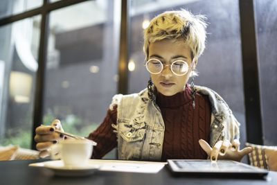 Woman wearing spectacles working on a tablet